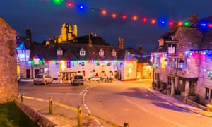 View of the lit-up ruin of Corfe Castle in Dorset, UK with Christmas lights decorating the village below.below.