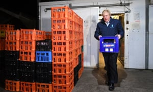 Prime minister Boris Johnson carries a crate during a visit to Greenside Farm Business Park in Leeds, ahead of Thursday's General Election.