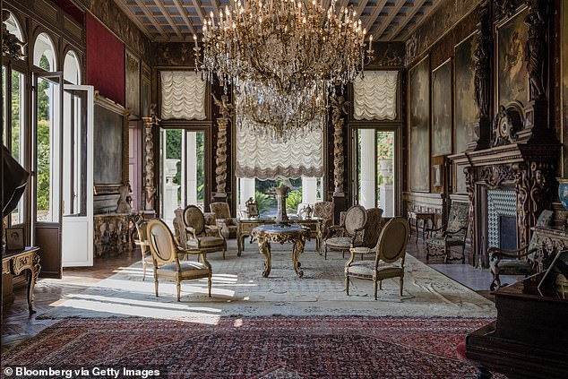 Armchairs and tables stand beneath chandeliers as 19th century portraits in ornate frames adorn the walls of a sitting room