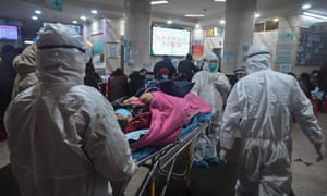 Medical staff wearing protective clothing arrive with a patient at the Wuhan Red Cross hospital in Wuhan on Saturday.