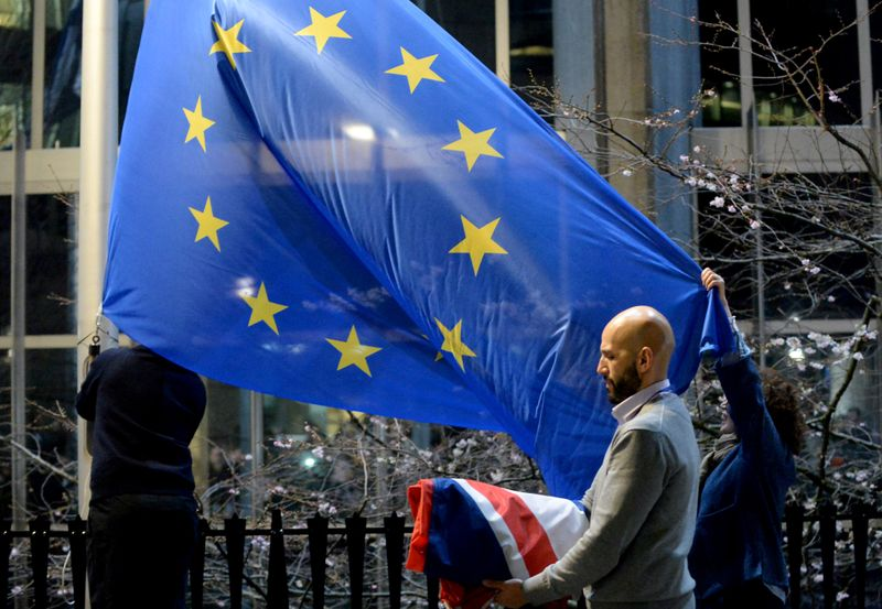© Reuters. FILE PHOTO: Workers replace the British flag outside the European Parliament building with the European Union flag, as Britain leaves the European Union, in Brussels