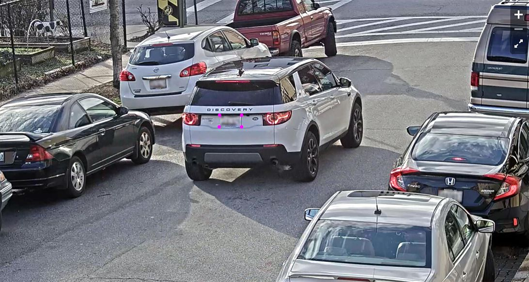 A car drives down a street with its license plate targeted by a camera.