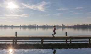 A jogger at De Kralingse PlasA jogger on the jetty on de Kralingse Plas, a lake in the middle of Rotterdam. In the background a nice view of the skyline of the city.