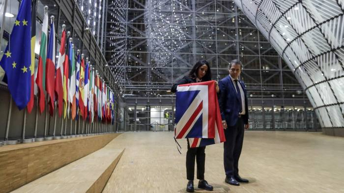 EU Council staff members remove the United Kingdom's flag from the European Council building in Brussels on Brexit Day, January 31, 2020. - Britain leaves the European Union at 2300 GMT on January 31, 2020, 43 months after the country voted in a June 2016 referendum to leave the block. The withdrawal from the union ends more than four decades of economic, political and legal integration with its closest neighbours. (Photo by OLIVIER HOSLET / POOL / AFP) (Photo by OLIVIER HOSLET/POOL/AFP via Getty Images)