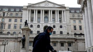 A man wearing protective face mask walks past the Bank of England in the City of London