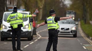 """Police officers from North Yorkshire Police stop motorists in cars to check that their travel is """"essential"""", in line with the British Government""""s Covid-19 advice to """"Stay at Home"""", in York, northern England"""