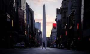 A person crosses an empty street in Buenos Aires, Argentina, 27 March 2020.