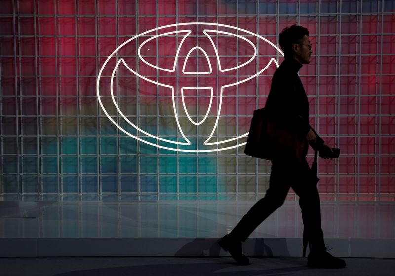 © Reuters. FILE PHOTO: A man walks past a Toyota logo at the Tokyo Motor Show