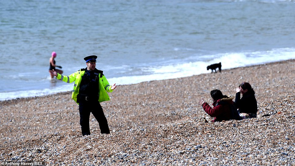 A police officer asks people to leave the beach in Brighton as the UK continues in lockdown during the outbreak of the Covid-19 virus