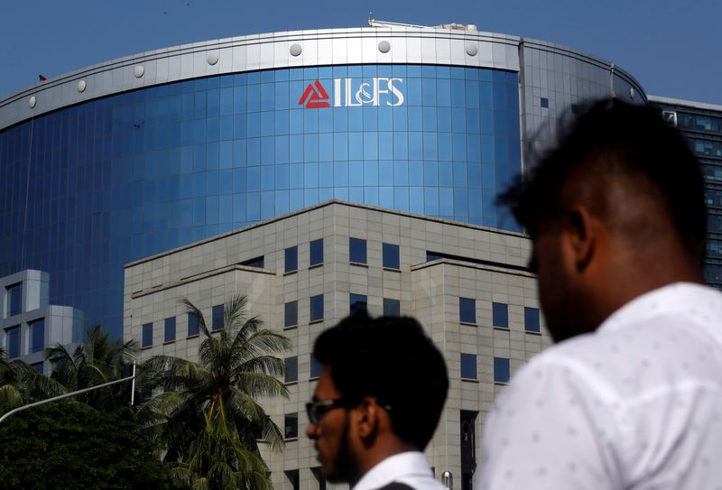 © Reuters. FILE PHOTO: People walk past a building of IL&FS outside its headquarters in Mumbai