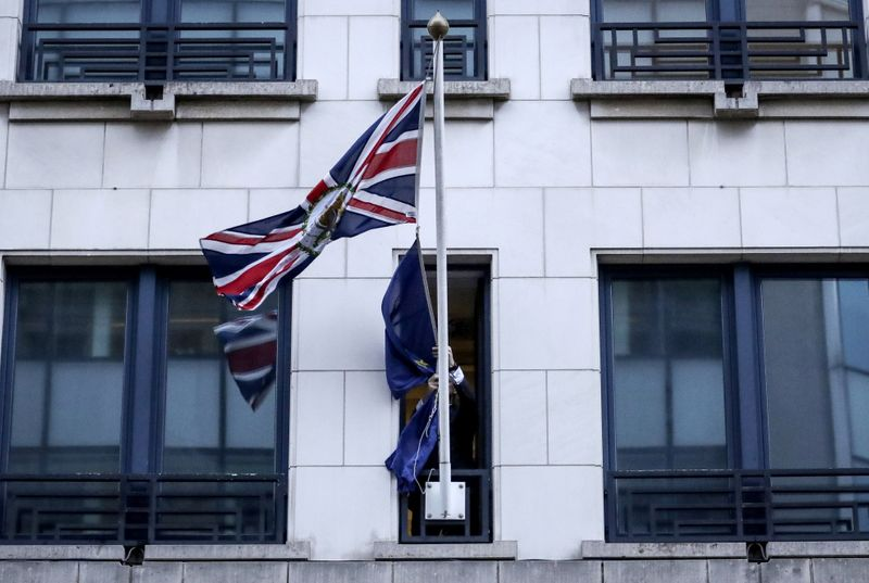 © Reuters. An official removes the EU flag from Britain's Permanent Representation to the EU in Brussels