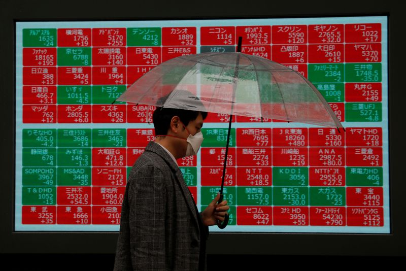 © Reuters. A visitor wearing protective face mask, following an outbreak of the coronavirus, walks past in front of a stock quotation board outside a brokerage in Tokyo