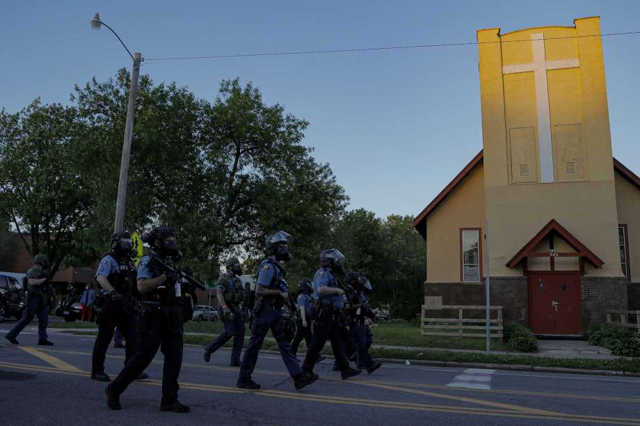 FILE - St. Paul Police officers move in on a crowd past a church, Thursday, May 28, 2020, in St. Paul, Minn.  The Rev. Charles Graham and other Twin Cities faith leaders who minister to communities historically ravaged by racial injustice know their neighborhoods are also the most vulnerable to poverty and crime. Most of the worst looting and vandalism this week struck long-established Native and African American areas that more recently became home to large groups of Hmong, Somali and Latino migrants. Photo: Julio Cortez, AP / Copyright 2020 The Associated Press. All rights reserved.