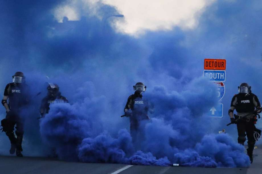 Police in riot gear walk through a cloud of blue smoke as they advance on protesters near the Minneapolis 5th Precinct, Saturday, May 30, 2020, in Minneapolis. Protests continued following the death of George Floyd, who died after being restrained by Minneapolis police officers on Memorial Day. Photo: John Minchillo, AP / Copyright 2020 The Associated Press. All rights reserved.