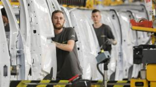 Factory employees work on a car assembly line at the Renault factory, in Maubeuge