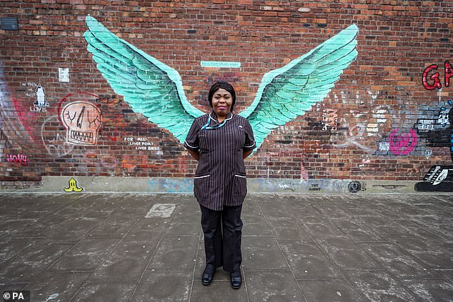 Susan Tay, a community matron at Mersey NHS Care, stands in front of the 'Liver Bird Wings' artwork by Paul Curtis at Liverpool's Baltic Triangle