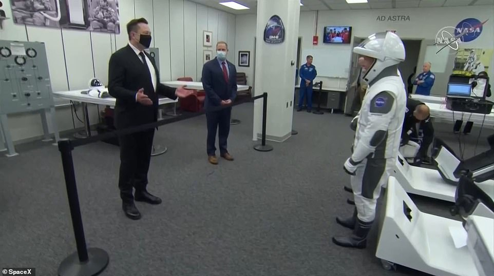 Musk (left) greeted Behnken and Hurley before today's launch while wearing a mask and social distancing