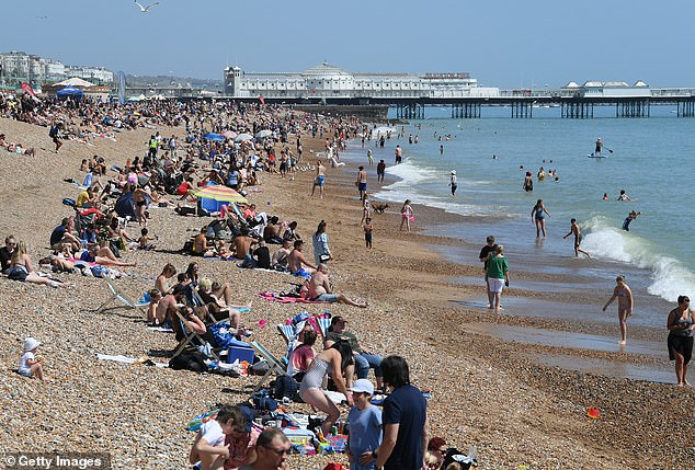 People pictured visiting Brighton beach during the UK's bank holiday yesterday. Scientists warn that summer poses its own risks to public health as the summer heat, which is often dry, can cause the droplets — deemed the primary form of transmission — to evaporate and form aerosols which can spread further