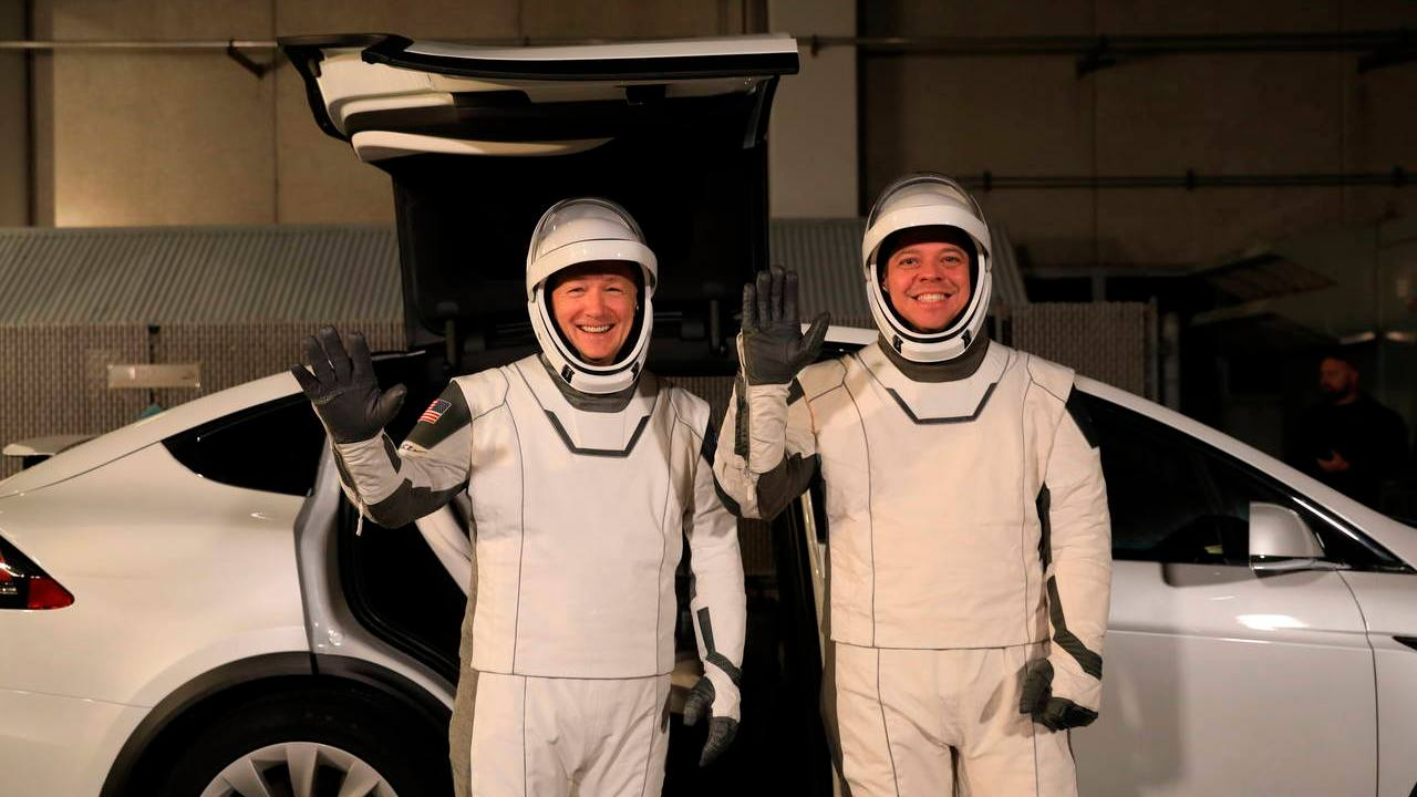 astronauts Doug Hurley, left, and Robert Behnken pose in front of a Tesla Model X at a SpaceX launch dress rehearsal, at Kennedy Space Center Image credit: AP