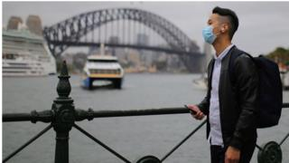 A man wears a face mask in front of the Sydney Harbour Bridge in Sydney, Australia.