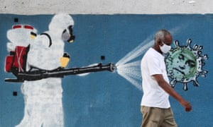 A man walks next to graffiti depicting a cleaner wearing protective gear spraying a virus with the face of Brazil's President Jair Bolsonaro, in Rio de Janeiro, Brazil, 12 June 2020.