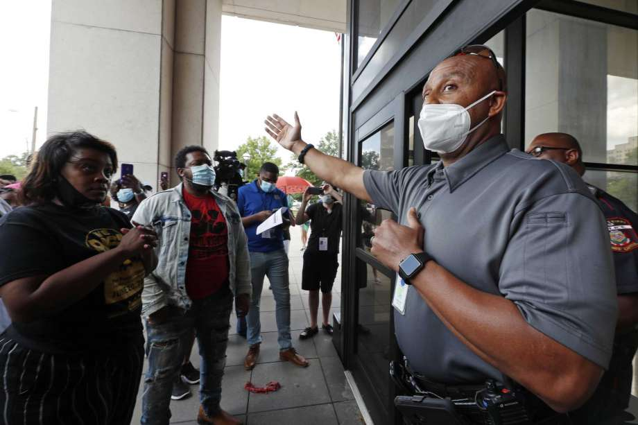 A Capitol police official explains the Walter Sillers State Office Building is closed to the public due to the coronavirus pandemic during a protest Friday, June 5, 2020, in Jackson, Miss., over Mississippi Attorney General Lynn Fitch's recent decision to drop a manslaughter charge against former Columbus Police Officer Canyon Boykin. Boykin, who is white, had been charged in the October 2015 shooting death of an African American man, Ricky Ball. Ball's family intended to deliver a letter to Fitch asking her to reopen the case but Capitol Police refused entry to the building. Photo: Rogelio V. Solis, AP / Copyright 2020 The Associated Press. All rights reserved