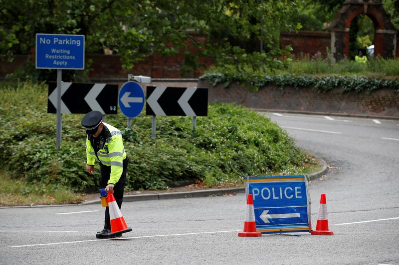 © Reuters. A police officer puts a traffic cone on a street following multiple stabbings reported in Reading
