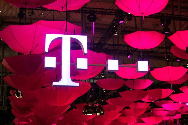 © Bloomberg. The T-Mobile logo for Deutsche Telekom AG's T-Systems unit, is seen suspended from the ceiling along with a collection of coloured umbrellas during the CeBit tech show in Hanover, Germany.