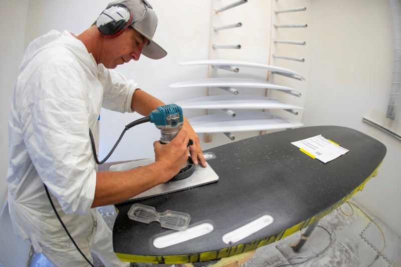 © Reuters. FILE PHOTO: James Black works on a soft INT surfboard at the INT surfboard factory in Carlsbad, California