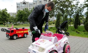 A man wearing a protective face mask and gloves sprays disinfectant while cleaning a rental electric baby car amid the coronavirus outbreak in a park in Kiev, Ukraine 2 June 2020.