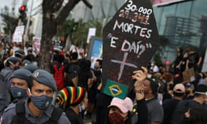"""An anti-government demonstrator wearing a protective face mask holds a poster with the message """"30,000 deaths, so what?"""", during a protest named """"Amazonas for Democracy"""" in Manaus, Brazil, 2 June 2020."""
