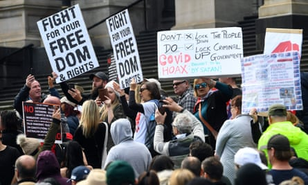 Anti-lockdown protesters hold placards on the steps of Victoria's state parliament in Melbourne on 10 May 2020.