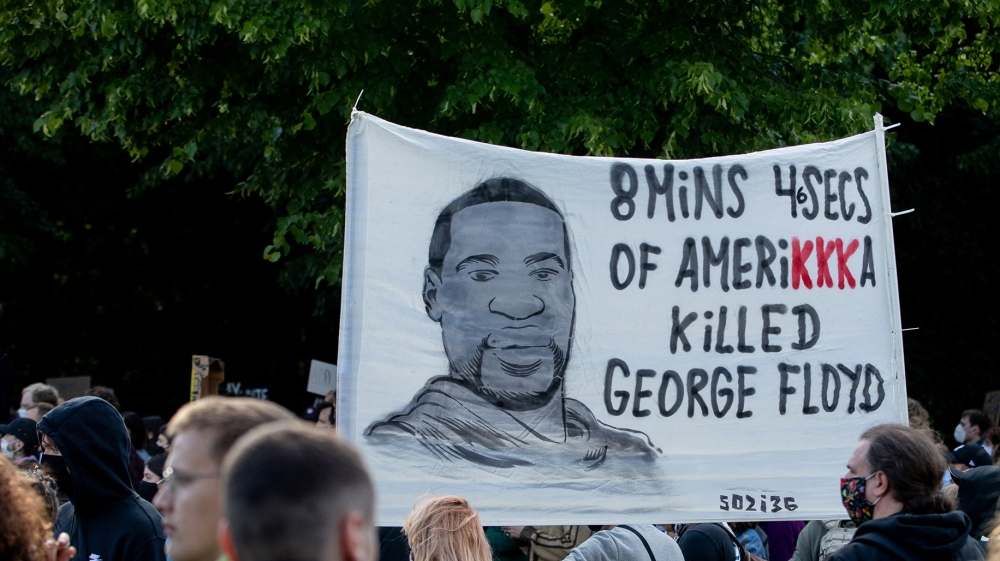 Participants in a rally against the violent death of African-American George Floyd by a white policeman hold a poster in front of the US Embassy with the words