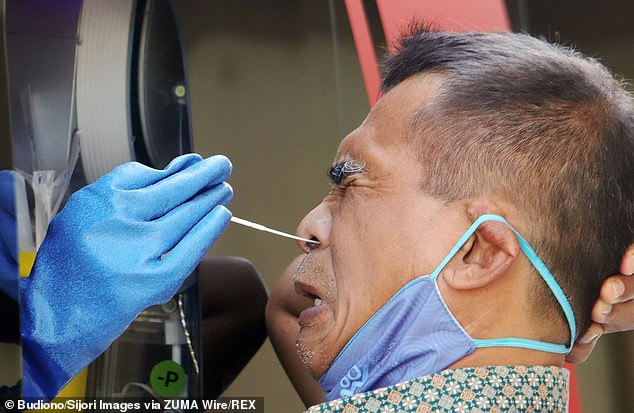 Professionally-done nasopharyngeal tests are known to be uncomfortable because the swab must go so far back into the person's nose (Pictured: A man getting tested in Surabaya, Indonesia)
