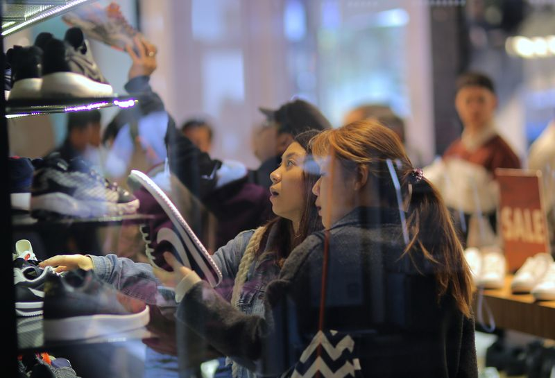 © Reuters. FILE PHOTO: Shoppers look at shoes on sale at a retail store in central Sydney