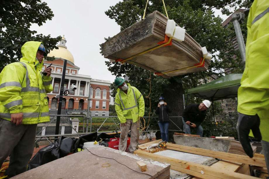 """Workers inspect the top cornice stone as it is lifted from the Shaw 54th Regiment memorial opposite the Statehouse, Friday, July 17, 2020, in Boston. Amid the national reckoning on racism, the memorial to the first Black regiment of the Union Army, the Civil War unit popularized in the movie """"Glory,"""" is facing scrutiny. Photo: Michael Dwyer, AP / Copyright 2020 The Associated Press. All rights reserved"""