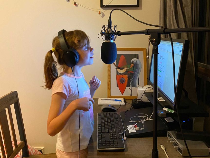 Young girl with headphones on talking into microphone in front of a computer.