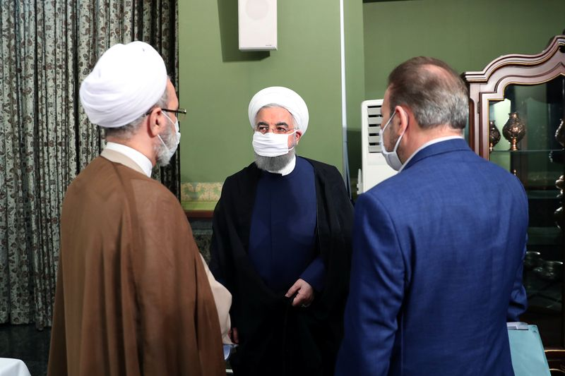 © Reuters. Iranian President Hassan Rouhani is seen wearing a face mask during a meeting, in Tehran