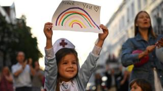 """A girl dressed as a nurse holds up a drawing of a rainbow with the words """"thank you"""" written on it"""