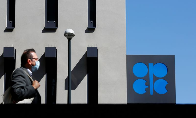 © Reuters. FILE PHOTO: A person passes the OPEC logo in front of its headquarters in Vienna