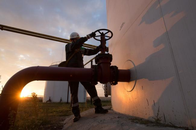 © Bloomberg. An employee turns a control valve on pipework beside a storage tank at an oil delivery point operated by Bashneft PAO in Sergeevka village, near Ufa, Russia, on Monday, Sept. 26, 2016. Bashneft distributes petroleum products and petrochemicals around the world and in Russia via filling stations. Photographer: Andrey Rudakov/Bloomberg