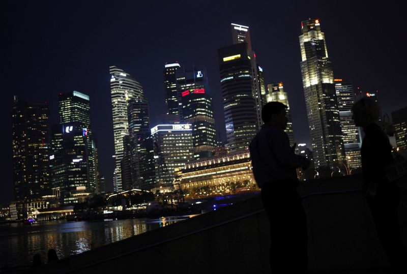 © Reuters. FILE PHOTO: People chat as the skyline of Singapore's financial district is seen in the background