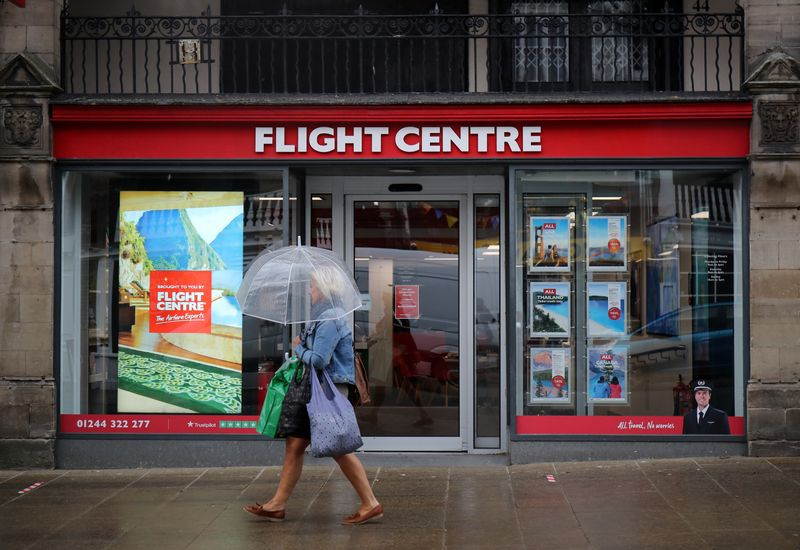 © Reuters. A woman walks past a Flight Centre travel agency in Chester