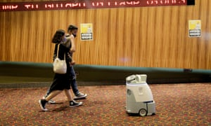 A couple walks past a cleaning robot at the lobby of a cinema in Singapore, 13 July 2020.