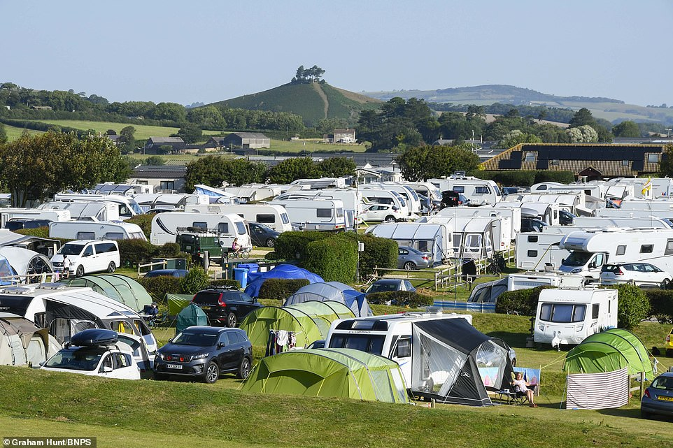 Highlands End Holiday Park at Eype in Dorset is packed with tents, caravans and camper vans on a hot day today