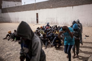 Female migrants queue in the prison yard as they are taken into buses to be transferred to another detention centre after they were sold by the militia group ruling the Surman detention camp in the west of Libya