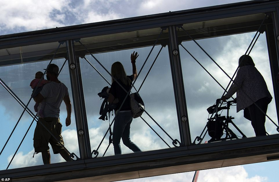 Passengers wave as they walk along a gangway as an airplane boards from Germany to Greece