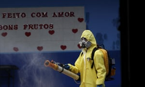 A government employee disinfects a public school in the Taguatinga neighborhood of Brasilia, Brazil, Tuesday, 28 July 2020.