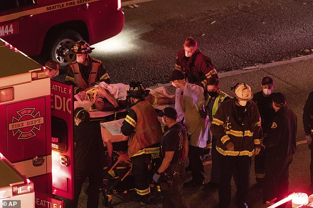 The two women are loaded into ambulances by first responders after they were hit by a speeding car on Interstate 5 in Seattle on Saturday