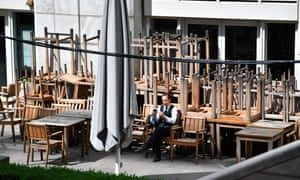 A person sits on a chair outside a closed pub in Canary Wharf in May